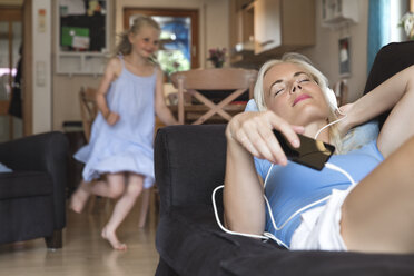 Mother lying on the couch listening music with headphones while her daughter moving in the background - MIDF000769