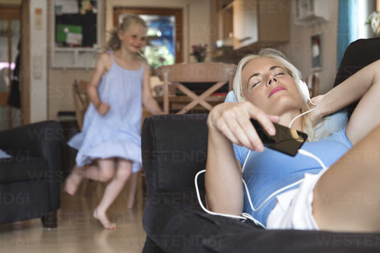 Mother lying on the couch listening music with headphones while her daughter moving in the background - MIDF000769 - Miriam Dörr/Westend61