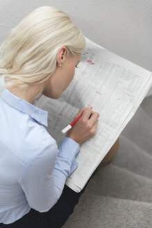 Back view of blond woman sitting on stairs marking informations at newspaper - MIDF000772