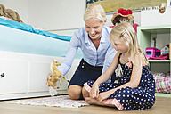 Businesswoman playing with her little daughter at children's room - MIDF000778
