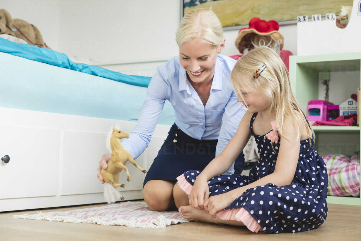 Businesswoman playing with her little daughter at children's room - MIDF000778 - Miriam Dörr/Westend61