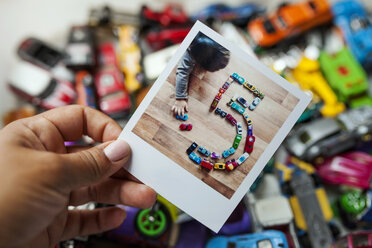 Polaroid of a little kid playing with his cars making a number five - VABF000711