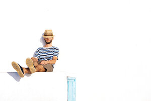 Man with straw hat and striped t-shirt sitting on spur leaning against white wall - GEMF000926