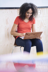 Young woman sitting under white board using laptop - RIBF000449