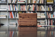 Wooden laptop on desk in library - RIBF000485