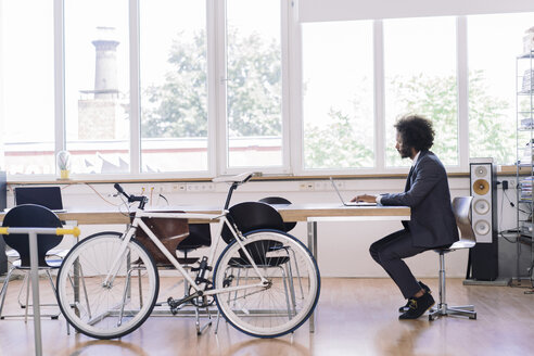Young businessman working in office with bicycle leaning against desk - RIBF000494