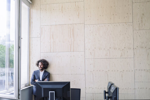 Young businessman standing by window, thinking - RIBF000569