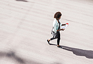 Walking businesswoman looking at document, seen from above - UUF008165