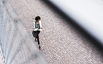 Walking businesswoman looking at documents, seen from above - UUF008171
