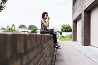 Young woman sitting on wall drinking coffee to go - UUF008195