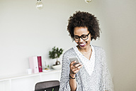 Smiling businesswoman  in office looking at her smartphone - UUF008210
