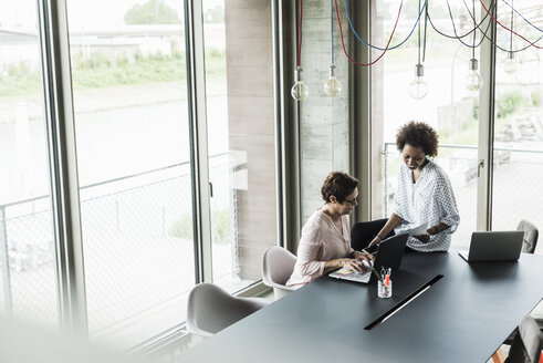 Two women working together in an office - UUF008216