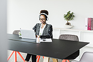 Businesswoman with headphones sitting at desk working with laptop - UUF008228