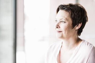 Portrait of smiling businesswoman looking through window - UUF008240