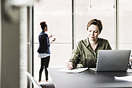 Businesswoman sitting at desk writing down something - UUF008255