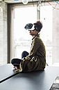 Woman in office sitting on conference table wearing virtual reality glasses - UUF008261