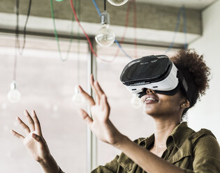 Woman in office using virtual reality glasses - UUF008264