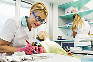 Orthodontist adjusting braces - ZEDF000226