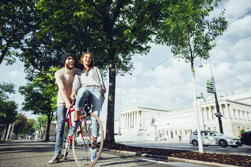 Austria, Vienna, young couple with bicycle near Parliament building - AIF000342