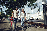 Austria, Vienna, young couple with bicycle in front of Parliament building - AIF000345