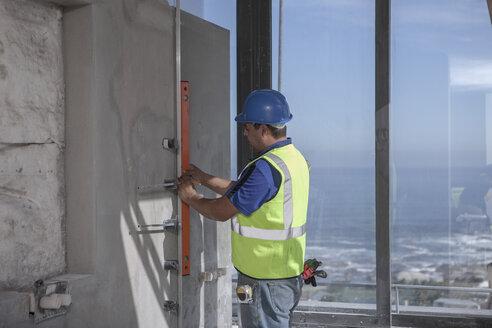 Construction worker using spirit level - ZEF009163