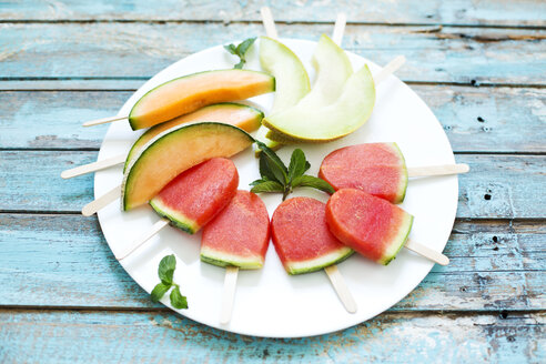 Plate of homemade watermelon ice lollies, slices of Galia and Cantaloupe melon - MAEF011913