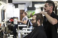 Barber combs hair of customer - ZEF009199