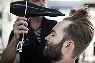 Barber blow-drying hair of a customer - ZEF009205