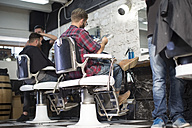 Customer reads magazine while seated at the barbershop - ZEF009217