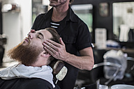 Barber measures on customers head before haircut at the barbershop - ZEF009220