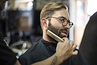 Barber combs beard of customer - ZEF009223