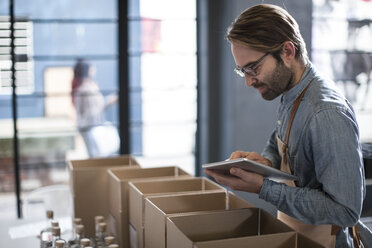Man surrounded by cardboard boxes using digital tablet - ZEF009238