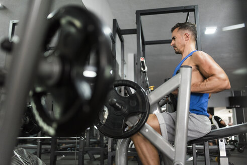 Man training with back exercise machine in gym - JASF000993