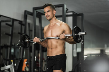 Man lifting barbell in gym - JASF000999