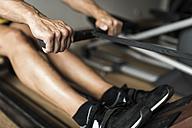 Man exercising at rowing machine in gym - JASF001002