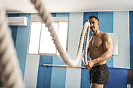 Man exercising with rope in gym - JASF001008