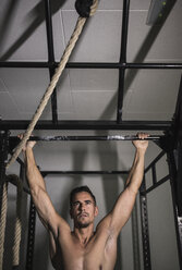 Man hanging at bar at power rack - JASF001014