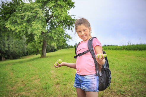 Smiling girl collecting apples on a meadow - VTF000535