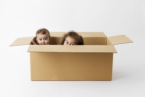 Two little children hiding together in a cardboard box - LITF000386