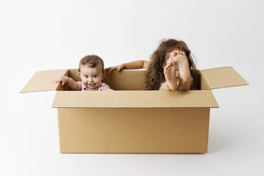 Two little children sitting together in a cardboard box - LITF000389