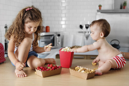Little girl and her baby brother having snack together on the kitchen counter - LITF000407