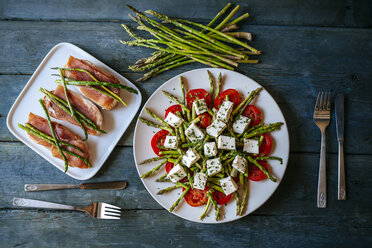 Plate of green asparagus, tomatoes and sheep cheese and plate of bread with cured ham and grilled asparagus - KIJF000610