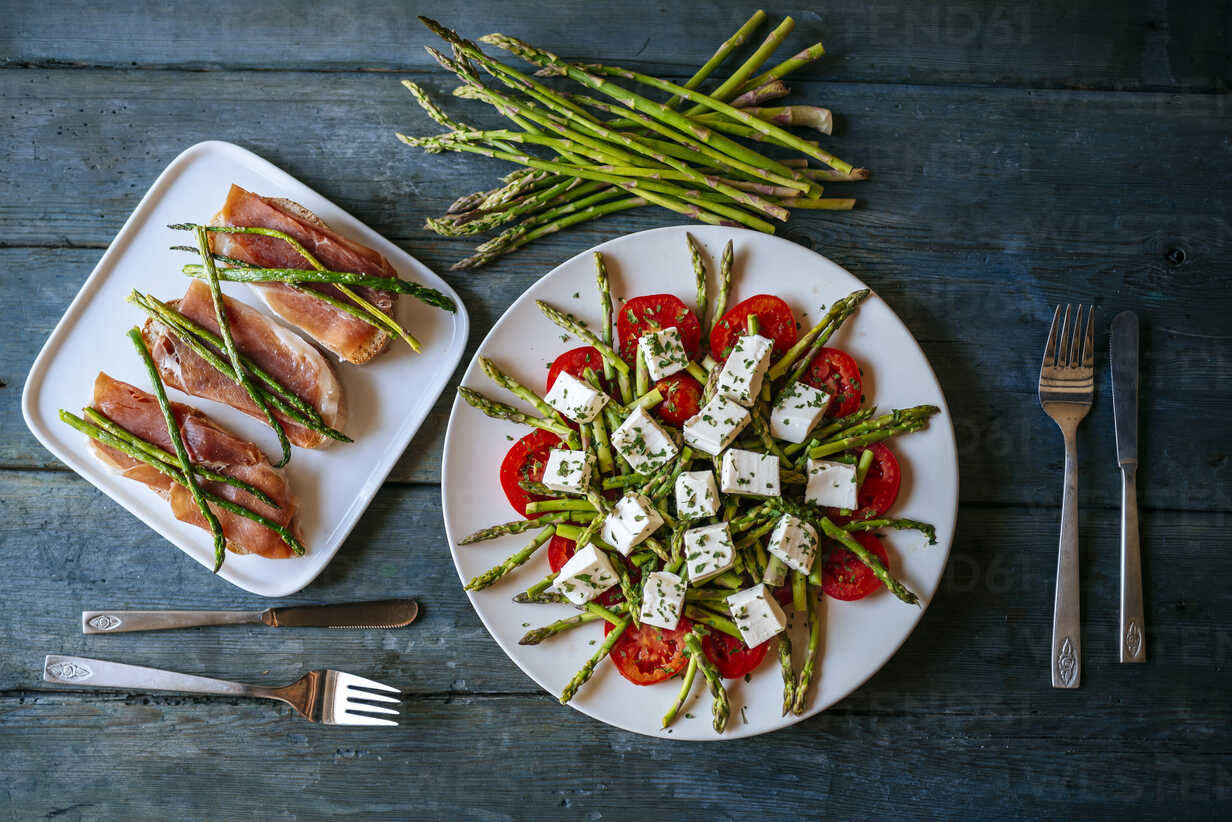 Plate of green asparagus, tomatoes and sheep cheese and plate of bread with cured ham and grilled asparagus - KIJF000610 - Kiko Jimenez/Westend61