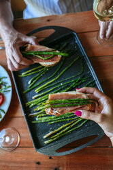 Hands taking bread slices with cured ham and grilled green asparagus - KIJF000613