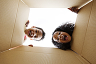 Two children looking together into a cardboard box - LITF000424