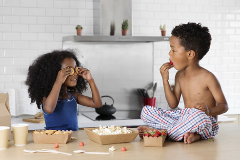 Little girl covering her eyes with cookies while brother watching her - LITF000436