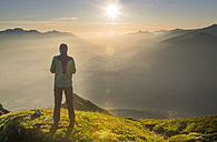 Austria, Tyrol, hiker looking at distance at sunrise - MKFF000319
