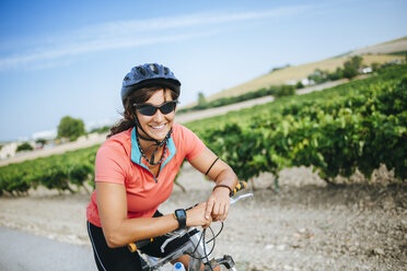 Spain, Andalusia, Jerez de la Frontera, Portrait of cyclist woman looking at camera while smiling - KIJF000616