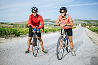 Spain, Andalusia, Jerez de la Frontera, couple, cyclists on a rural road between vineyards - KIJF000622