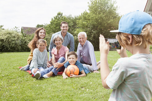 Boy taking picture of happy extended family in garden - RBF004760